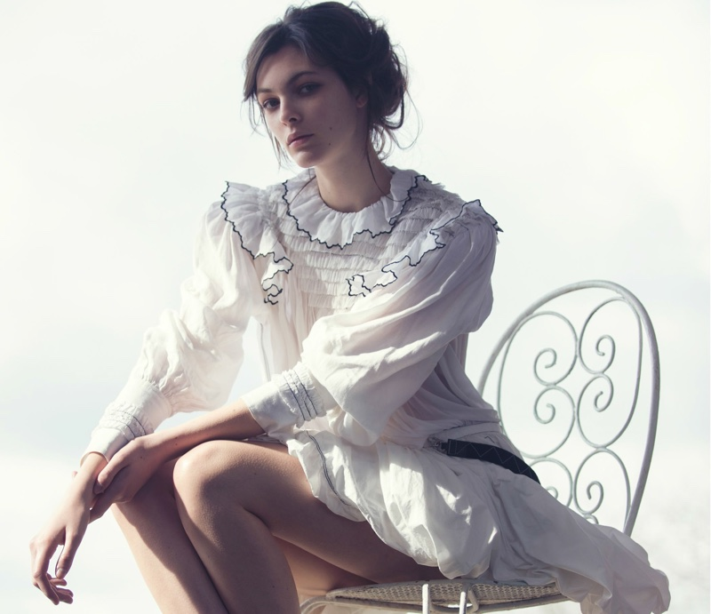 Wearing all white, Vittoria models Louis Vuitton blouse and bubble skirt