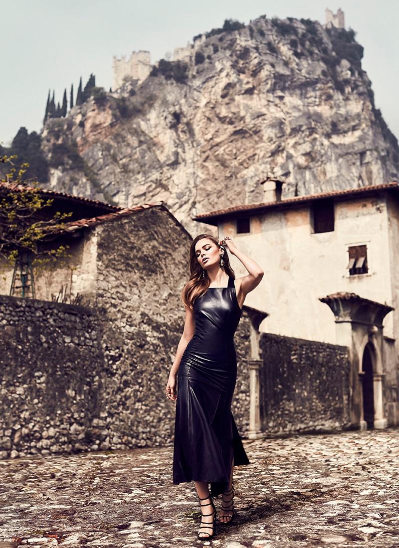 The model wears a black leather Hermes dress