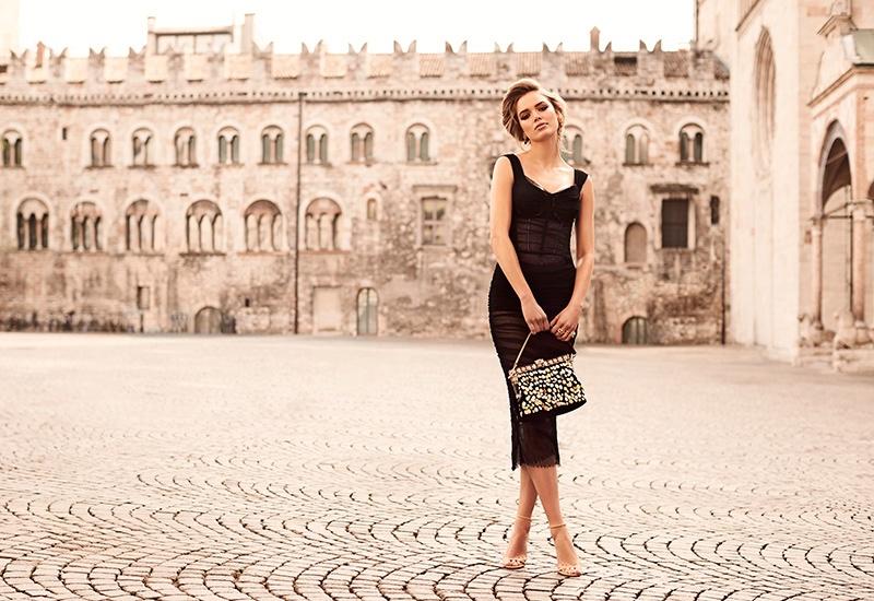 Zo Nowak wears a black Dolce & Gabbana dress and bags with Jimmy Choo heels