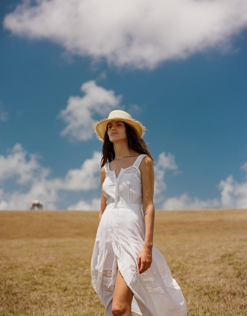 The model looks lovely in white wearing a LoveShackFancy dress with Sensi Studio hat