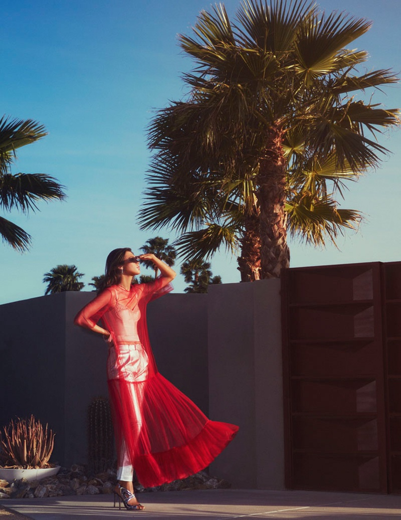 Catching the breeze, the brunette model wears sheer red dress