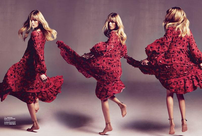 The model twirls in a red floral appliqué Michael Kors Collection dress