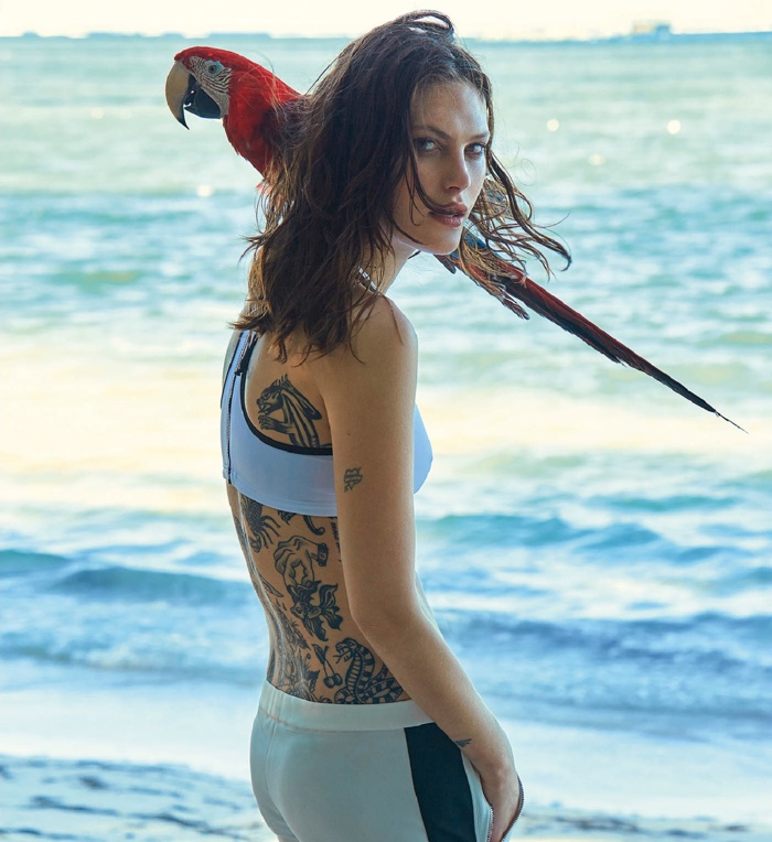 Posing on the beach, Catherine McNeil models with a parrot