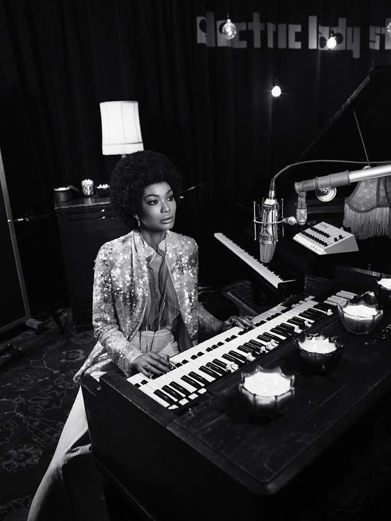 Sitting at a piano, Chanel Iman wears a sequin-embellished jacket