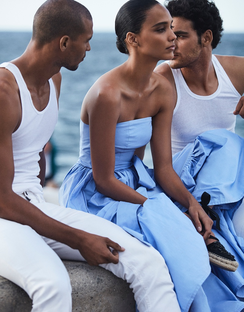Posing with two hunky male models, Cora Emmanuel wears strapless blue dress with espadrilles