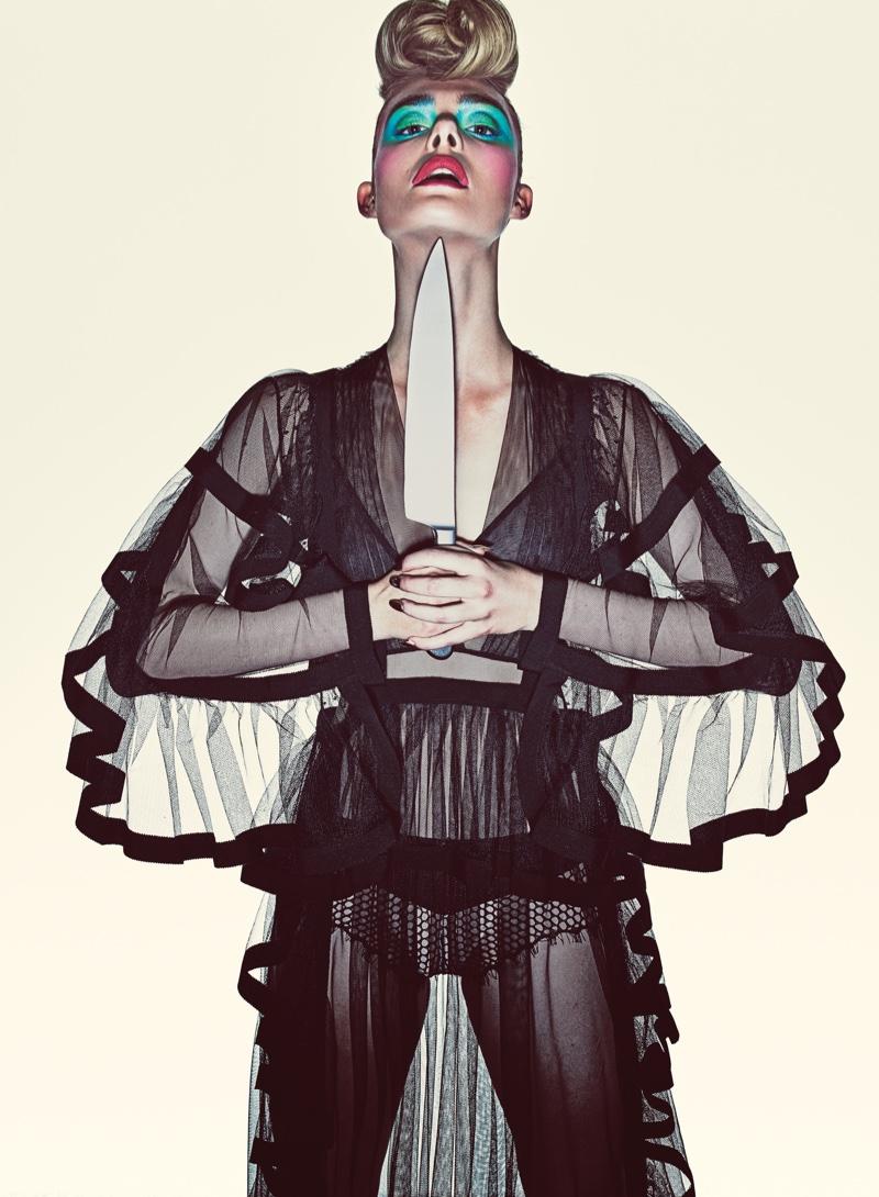 Posing with a dagger, Elle Fanning wears black lingerie