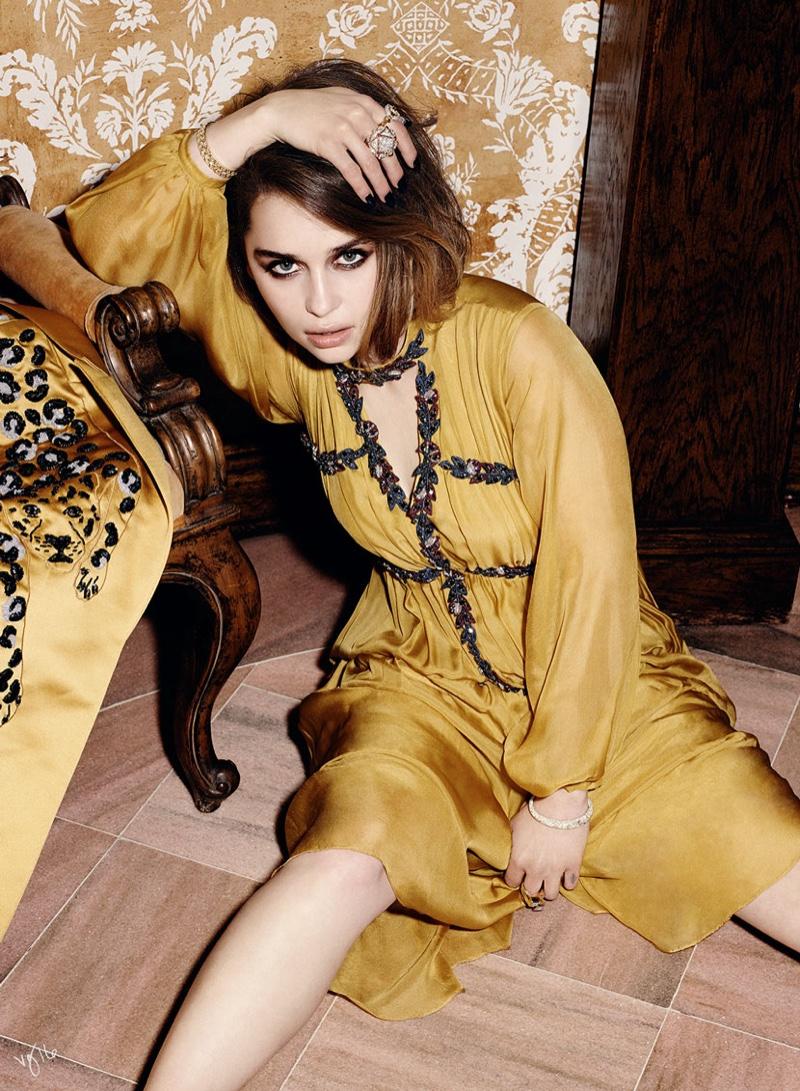 Posing on the floor, Emilia Clarke wears Disaya dress with glittering gems