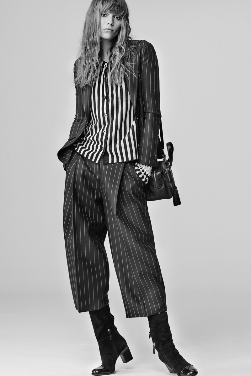 Model wears striped silk blouse, jacket and pants in pinstripe wool from Giorgio Armani's fall-winter 2016 collection