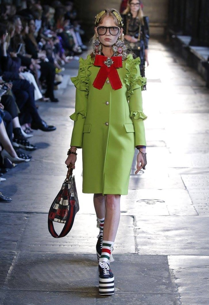 A model walks the runway at Gucci's resort 2017 show wearing a green coat with ruffle-embellished sleeves and platform sneakers