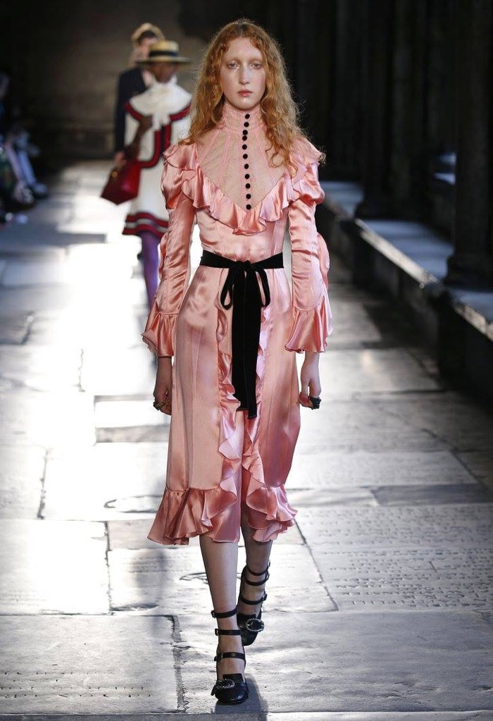 A model walks the runway at Gucci's resort 2017 show wearing a pink dress with a high-neckline and ruffle details