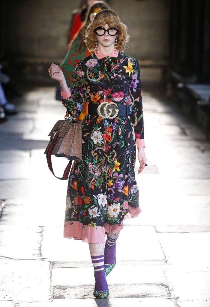 A model walks the runway at Gucci's resort 2017 show wearing a floral print dress with a belt featuring the Gucci logo
