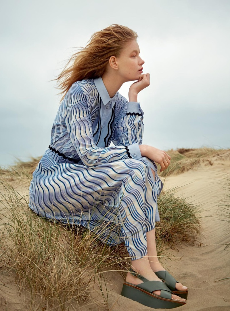The model poses on the beach wearing a Mary Katrantzou printed dress