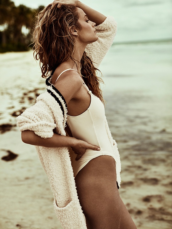 Kate Bock poses in cardigan sweater with white one-piece swimsuit