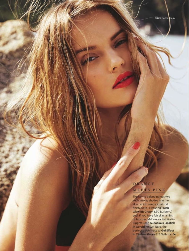 The blonde model wears a bold red lipstick shade