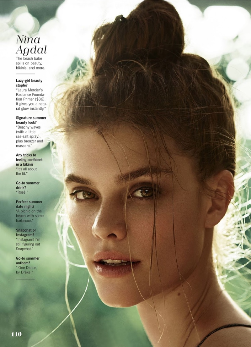 Nina Agdal wears her hair in a messy top knot hairstyle