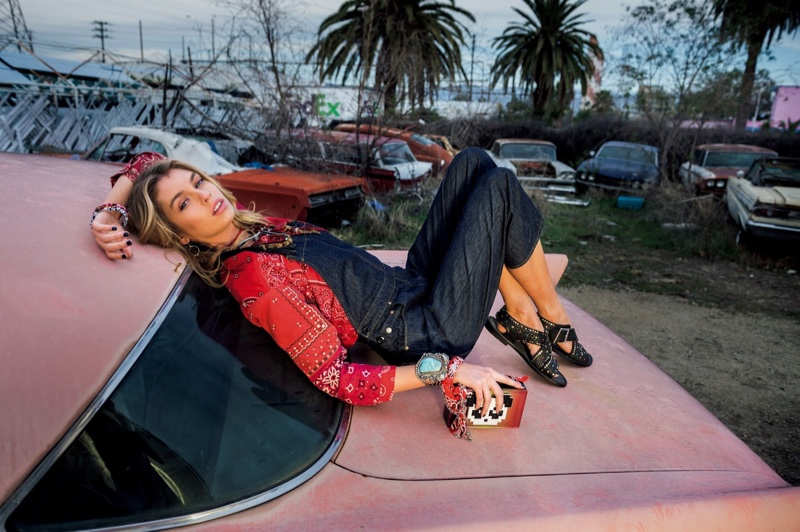 Posing on a car, Stella Maxwell wears denim overalls with red printed shirt