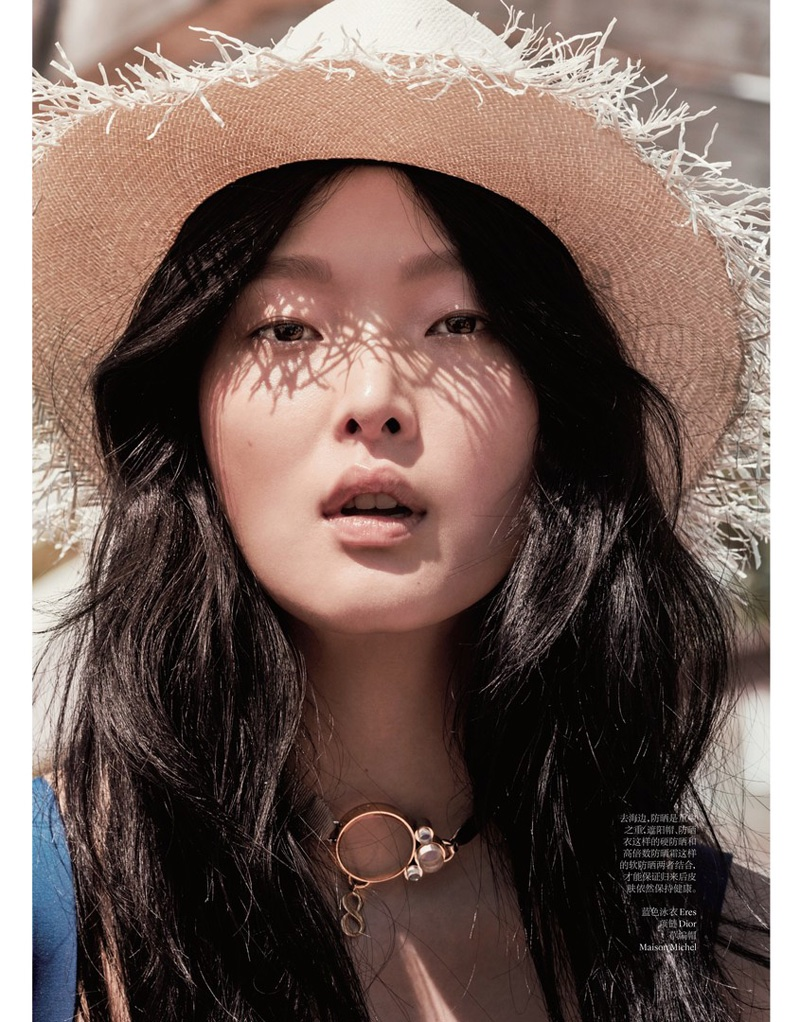 The model wears a straw hat with a wavy hairstyle