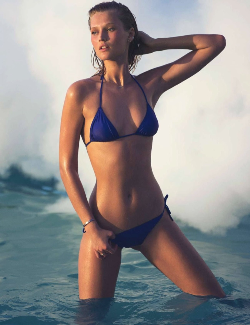 Posing at the beach, the blonde model sports a blue bikini from Petit Bateau