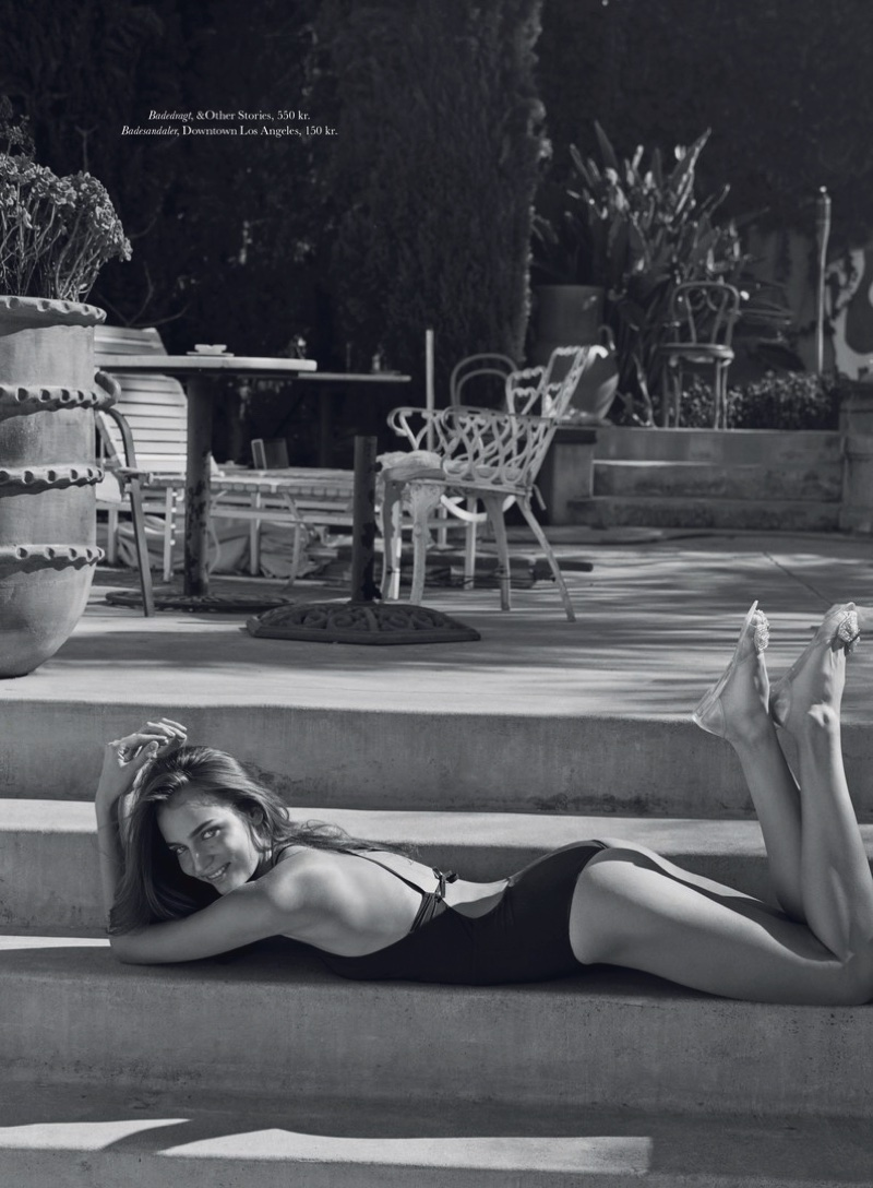 Photographed in black and white, Zuzanna wears a & Other Stories one-piece swimsuit