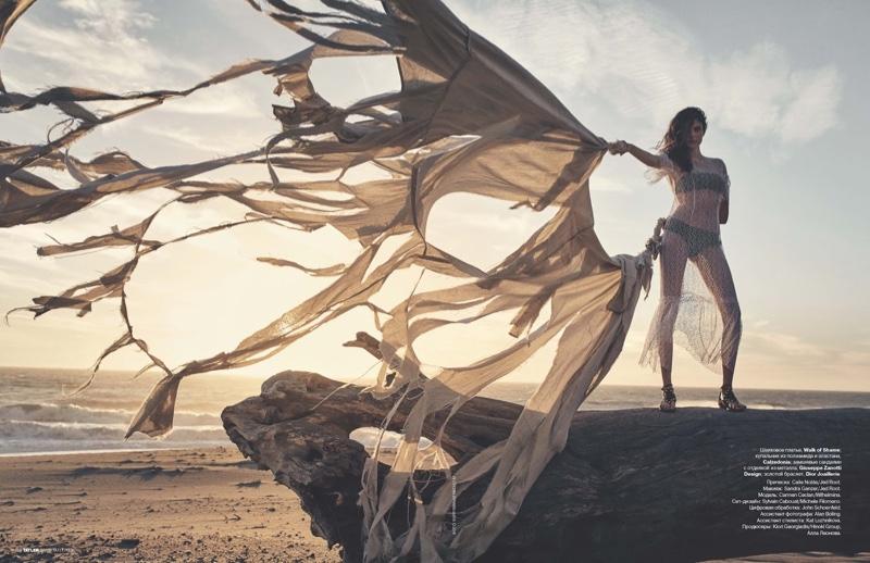 Carmen Ceclan raises tattered fabric while wearing Calzedonia swimsuit