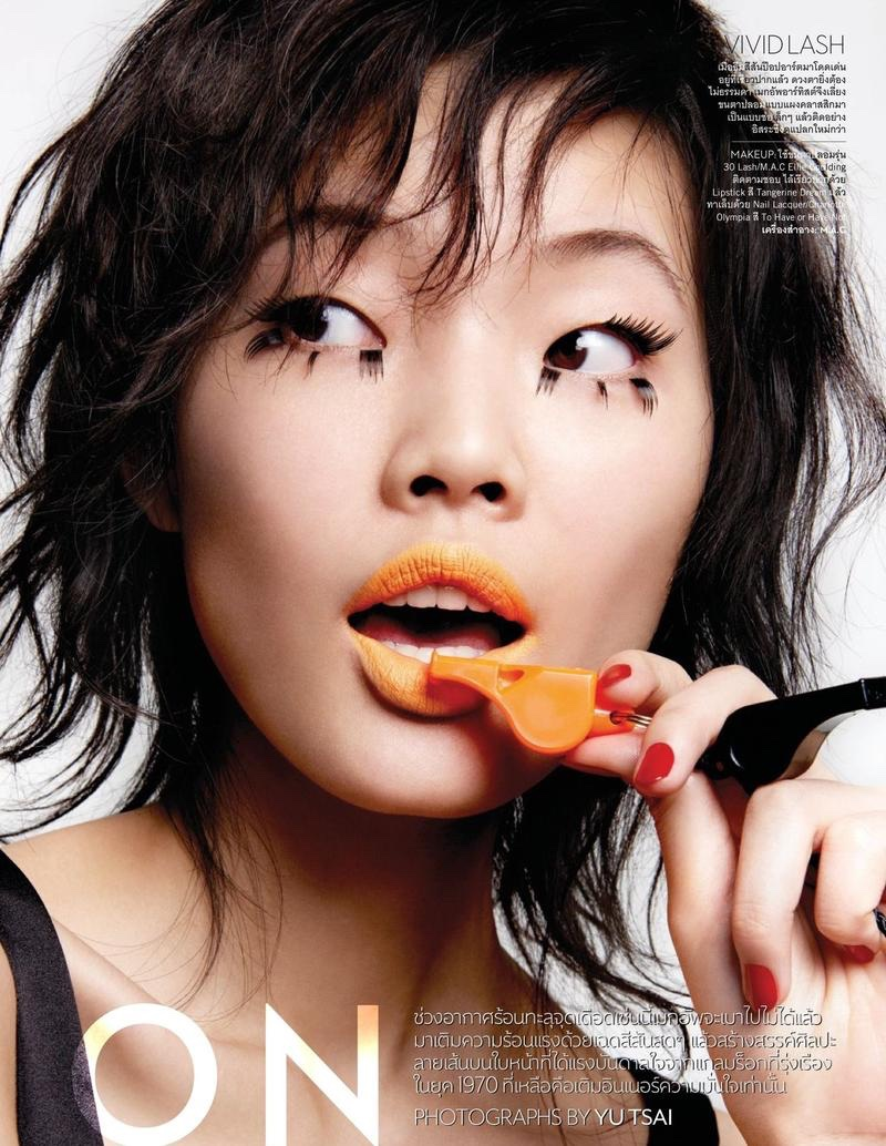 Chen Lin models feathery eyelashes with bright orange lipstick