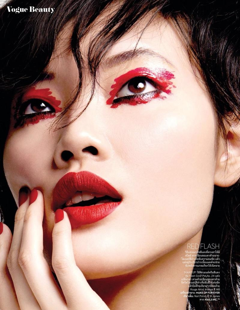 Chen Lin models red eyeshadow with matching lipstick and manicure