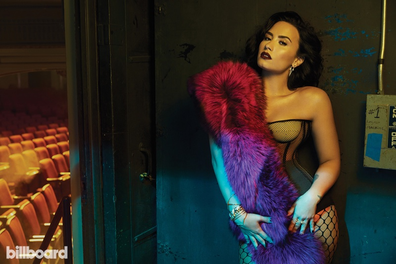 Demi Lovato poses in fuschia stole with corset top