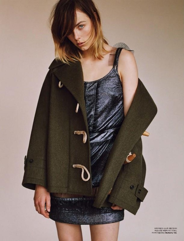 Edie Campbell poses in duffle coat with metallic dress