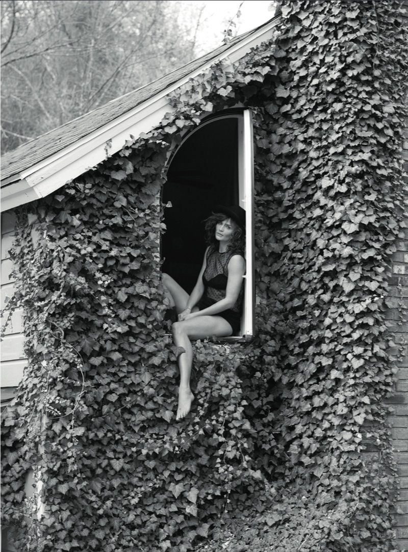 Photographed in black and white, Helena Christensen poses amidst vines