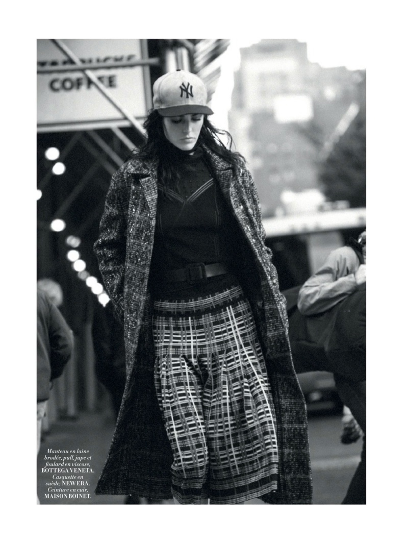 Photographed in black and white, Hilary Rhoda wears coat, sweater, pants and scarf from Bottega Veneta