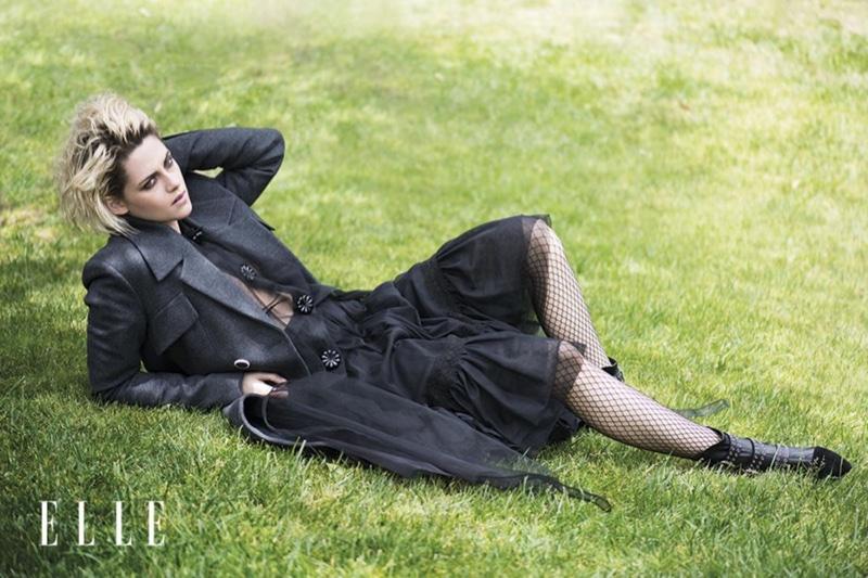 Kristen Stewart lounges in the grass wearing an all black ensemble