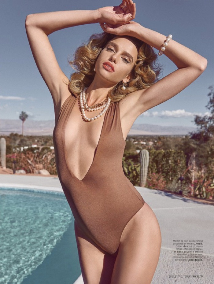 Masha wears a plunging one-piece swimsuit with pearl necklace