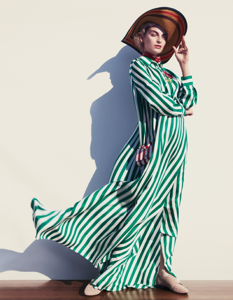 The model poses in Dolce & Gabbana striped caftan, Eugenia Kim straw hat and Jimmy Choo shoes