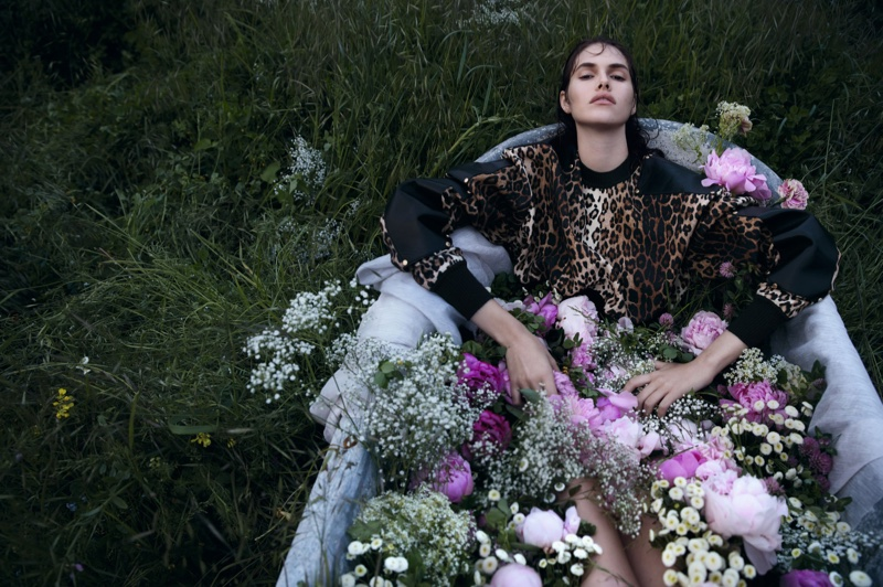 Taking a moment to relax, the model poses in a bathtub full of flowers