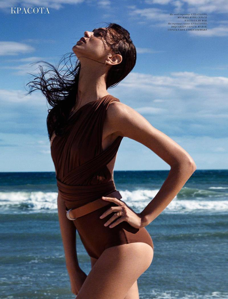The brunette model poses in brown swimsuit with ruched detail