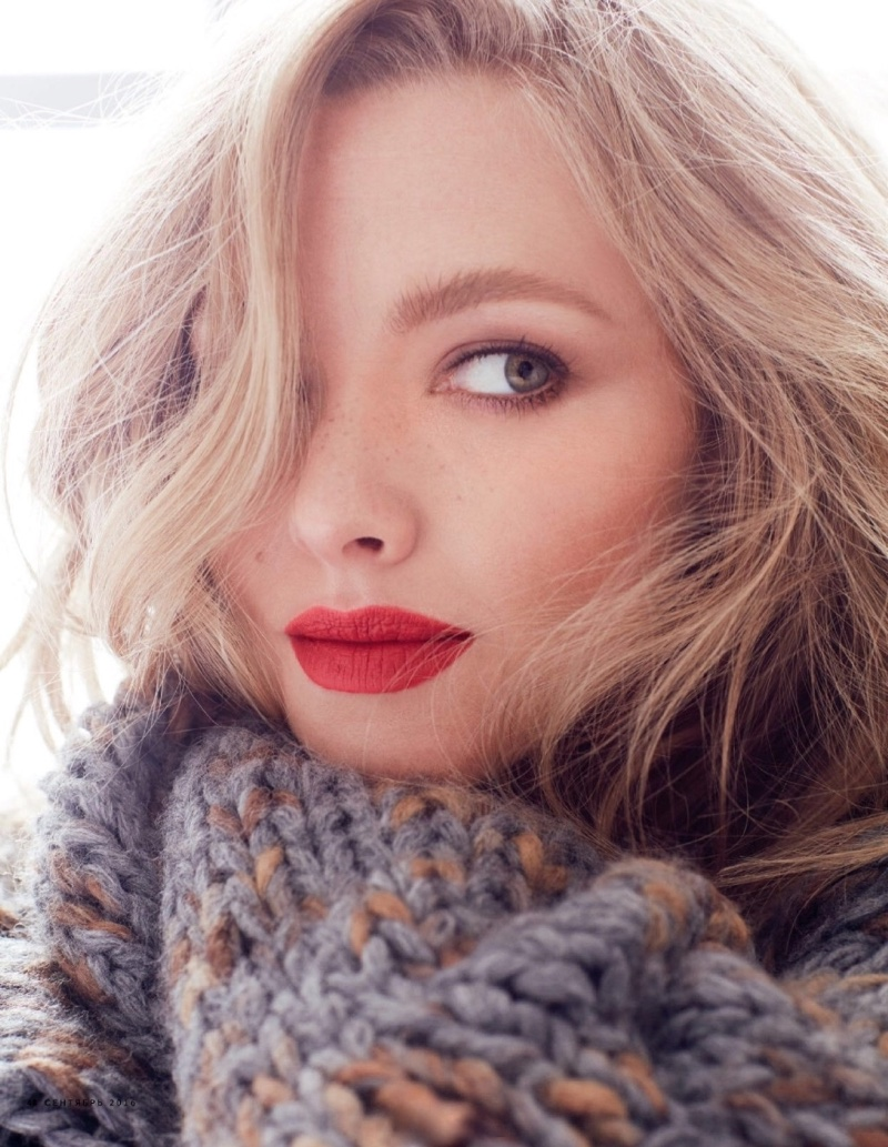 Posing in a chunky knit sweater, Amanda Seyfried models red lipstick shade