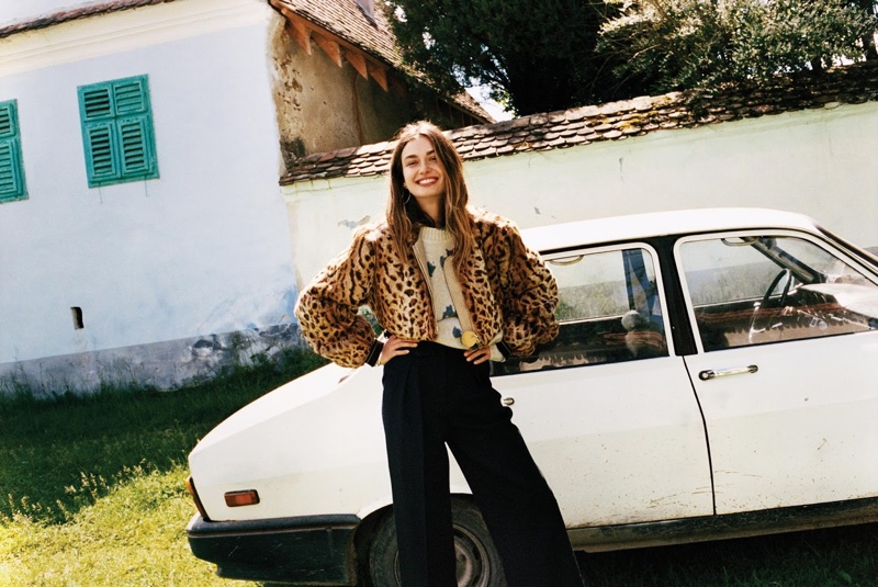 Posing next to a car, Andreea Diaconu wears Givenchy fur jacket with The Elder Statesman sweater and Lemaire pants