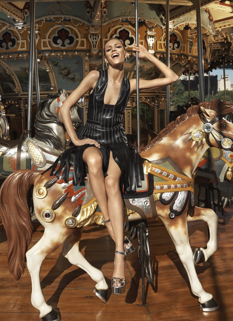 Sitting on a carousel, Anja Rubik is all smiles in leather fringed dress