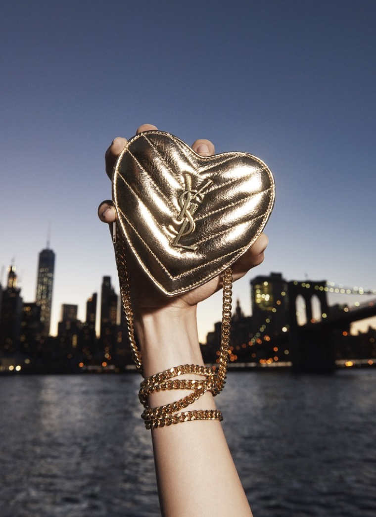 The Manhattan skyline serves as a backdrop to a heart-shaped Saint Laurent pouch