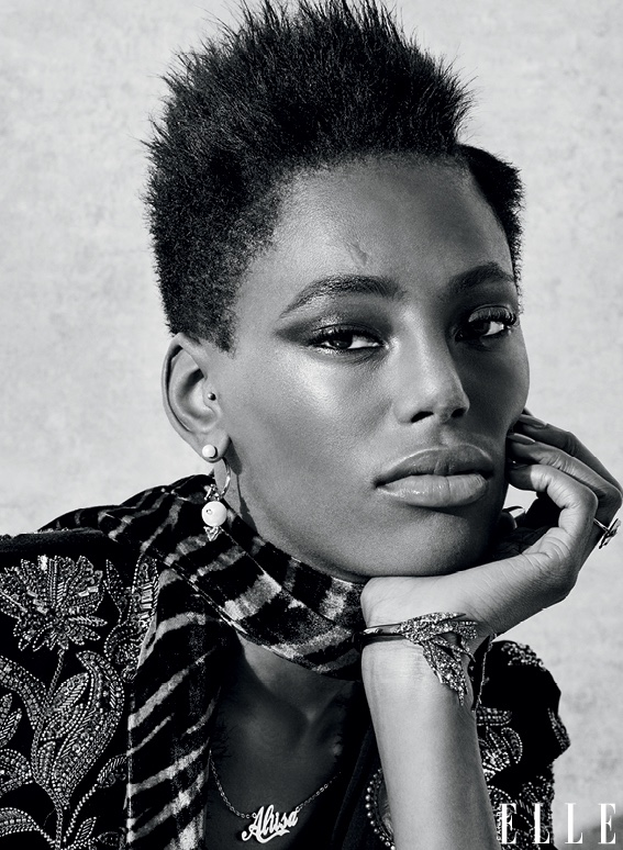 Model wears short natural hairstyle with trimmed sides