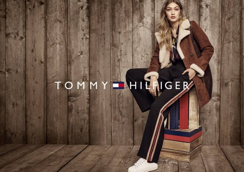 Gigi Hadid layers up in brown coat, striped pants and sneakers from Tommy Hilfiger
