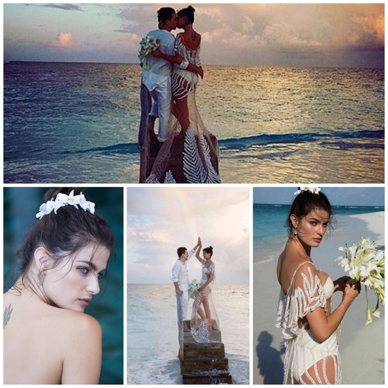 Isabeli Fontana poses at the beach wearing her sheer wedding dress and holding a white bouquet