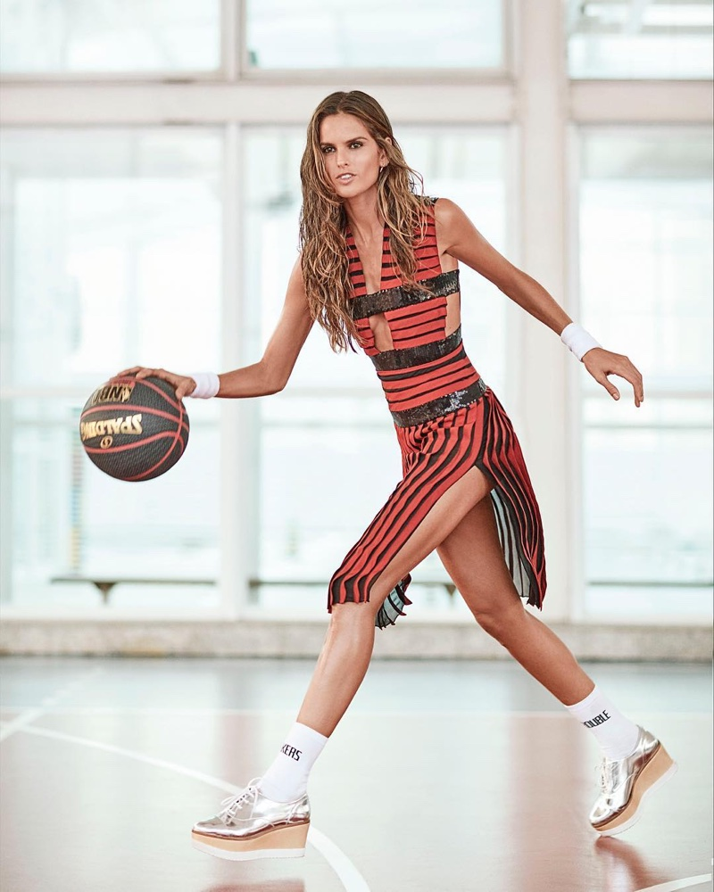 Posing with a basketball, Izabel Goulart wears striped dress with platform shoes