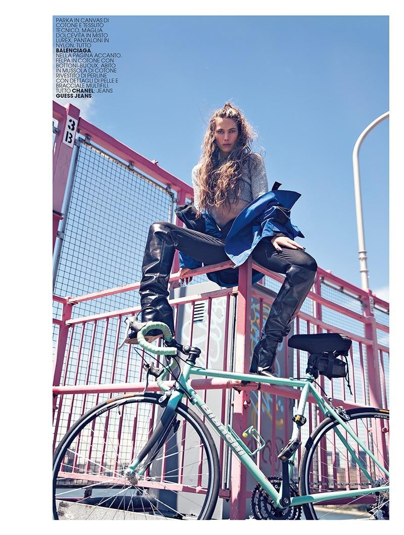 Posing on a bike, Jessica Miller wears parka, cropped sweater and pants from Balenciaga