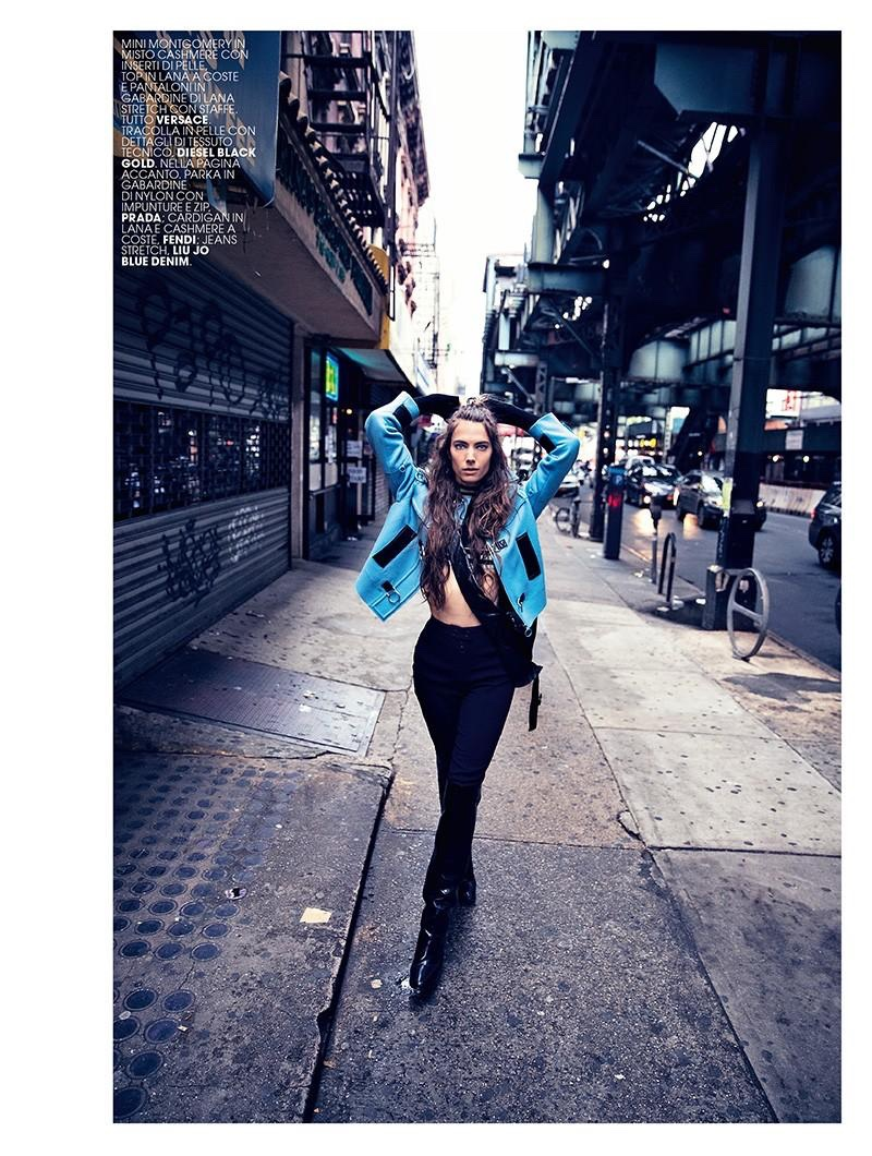 Hitting the streets, the model wears jacket, pants, sweater and boots from Versace