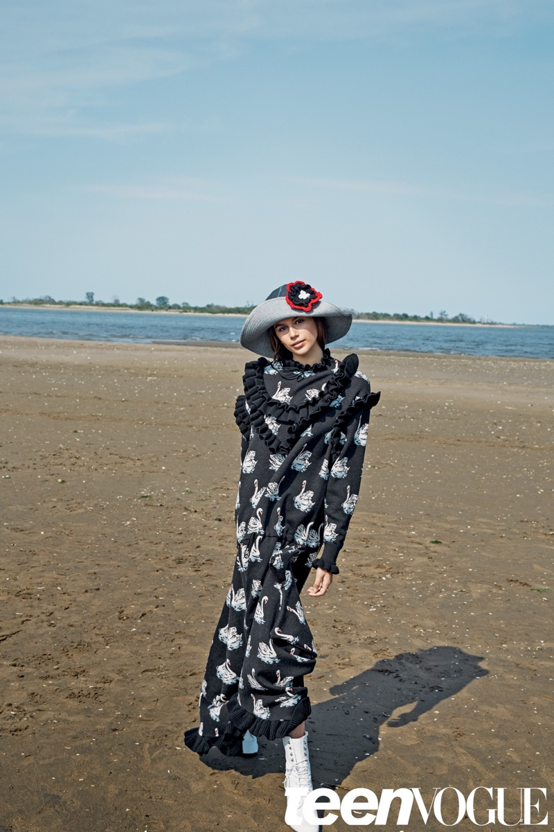 Kaia Gerber poses on the beach wearing a ruffle adorned Stella McCartney dress with Lola Hats hat