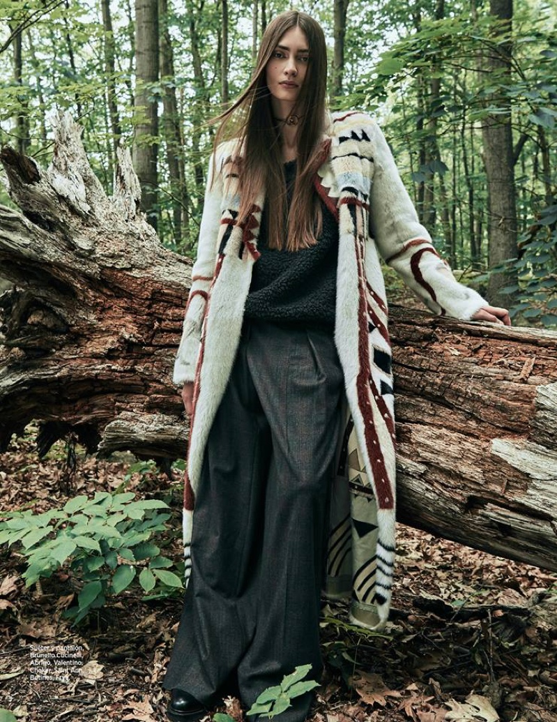The model lounges in Brunello Cucinelli sweater and pants with Valentino coat