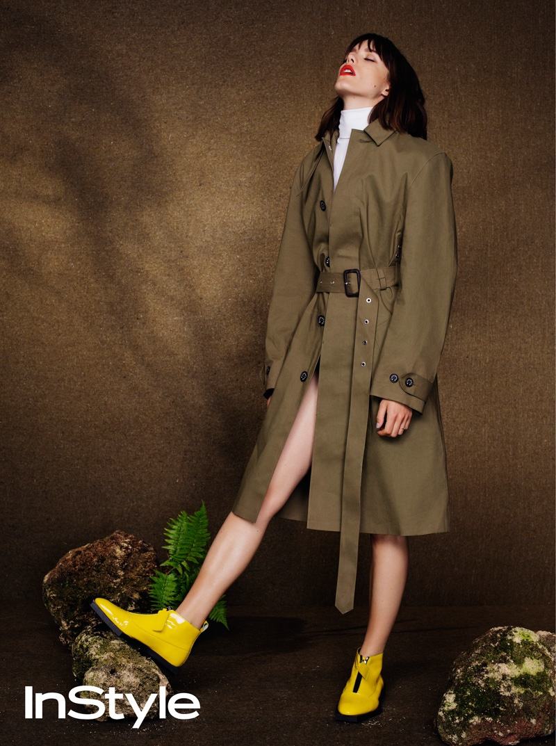 Stacy Martin poses in Khaki colored coat with yellow boots