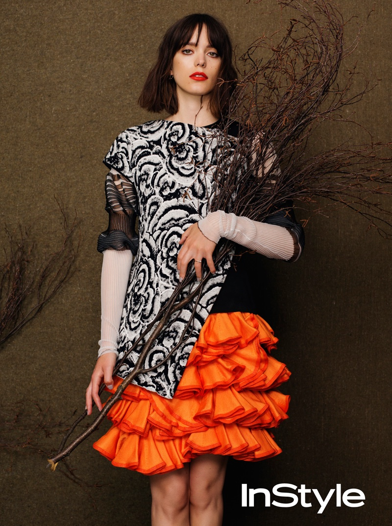 Stacy Martin poses in printed blouse with orange ruffled skirt