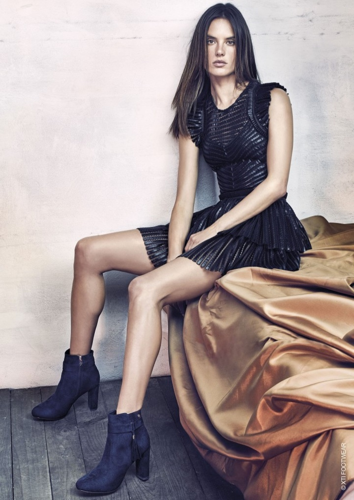 Model Alessandra Ambrosio poses in little black dress, and ankle boots from XTI